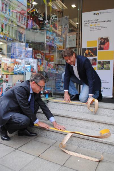 Thomas Hudovernik (Obmann Innenstadtverein) und Bernhard Leber (Geschäftsleiter BSVT) bekleben die Treppe vor dem Heiss Spielwarengeschäft.