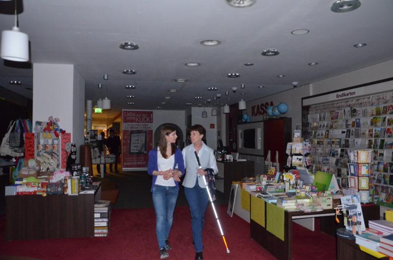 Eine freiwillige Helferin führt eine SChülerin unter der Dunkelbrille zur Lesung im Dunkeln