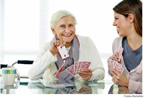 Junge und ältere Dame beim Kartenspielen.