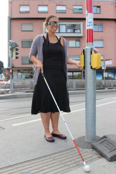 Eine junge Dame mit Simulationsbrille und Blindenstock an der Blindenampel. Credit: BSVT