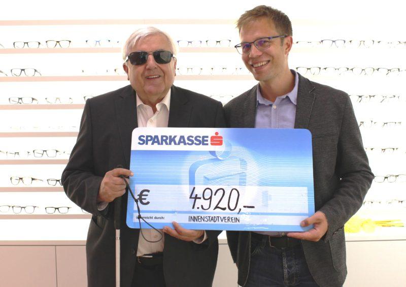 Ulrich Miller (Innenstadtverein) überreicht Klaus Guggenberger den Scheck.