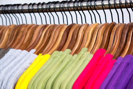 Bunte T-shirts auf Kleiderbügeln im Kleiderschrank