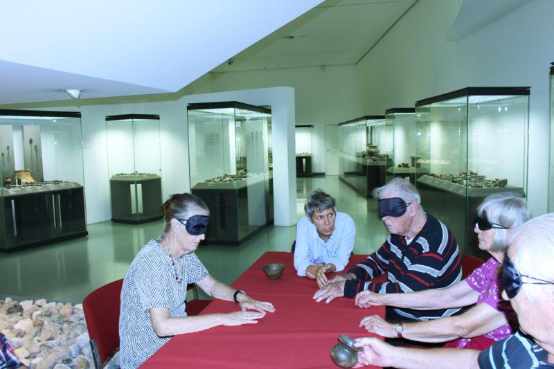 Blinde, sehbehinderte Menschen und sehende Teilnehmer mit Dunkelbrille erfühlen Jahrtausende alte Gegenstände. Foto: BSVT