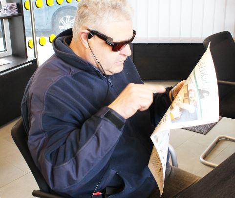 Eine Brille liest die Zeitung vor.