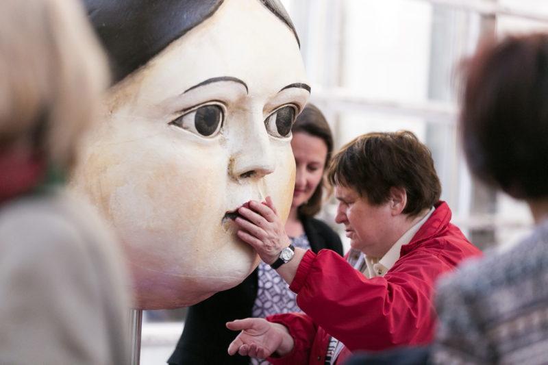Blinde Besucherin betastet einen überlebensgroßen Puppenkopf